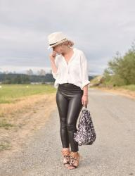 It's black and white:  styling vegan leather leggings with an oversized shirt, straw fedora, and beaded sandals