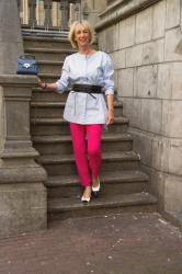 A pair of bright pink trousers, worn three ways